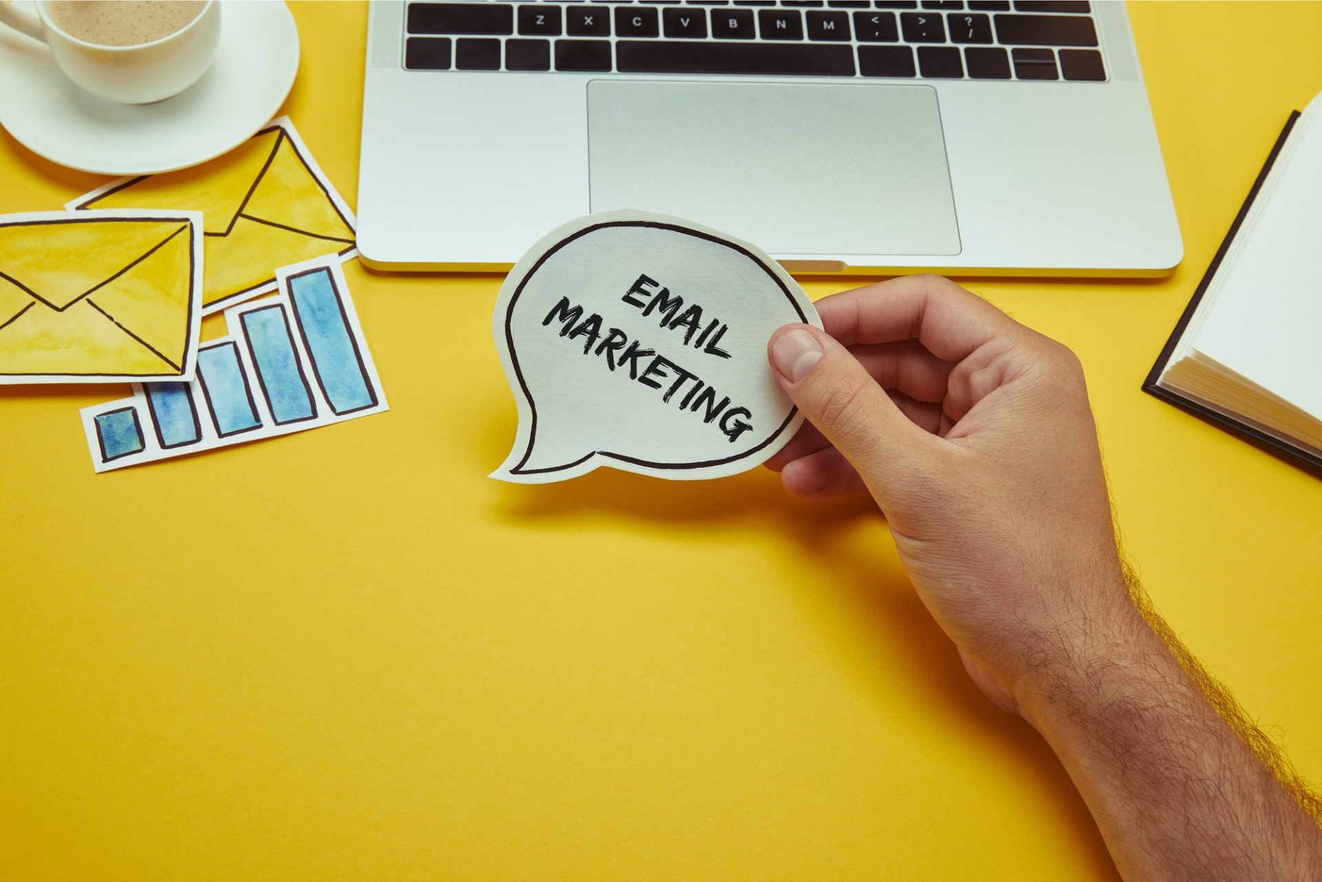 "cropped image of man holding speech bubble with""email marketing"" lettering near laptop"